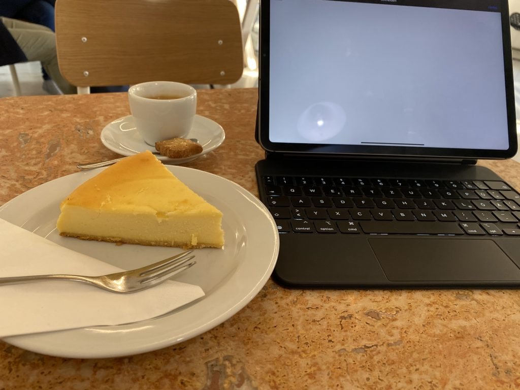 Picture of coffee and cheesecake at a coffee shop in preparation of learning Chinese. Besides there is a tablet.