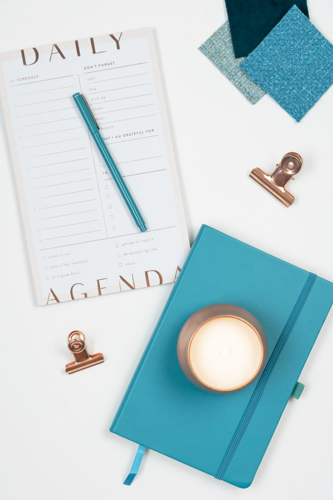 Planner tools in white and turquoise with a candle