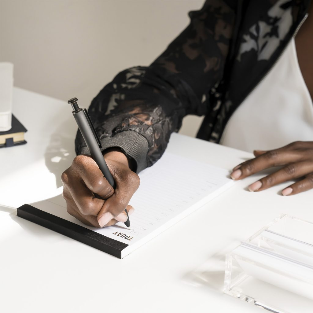 hand of a colored woman writing the strategies to handle toxic people on  white paper