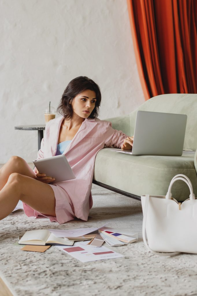 woman sitting on the floor with a book and a laptop. thinks about toxic people