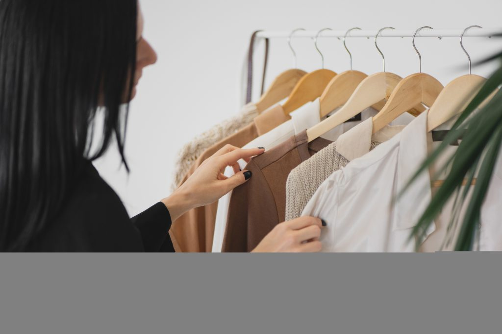 A woman with black hair looks up her clothes. She seems to think about how to decide which one to take.