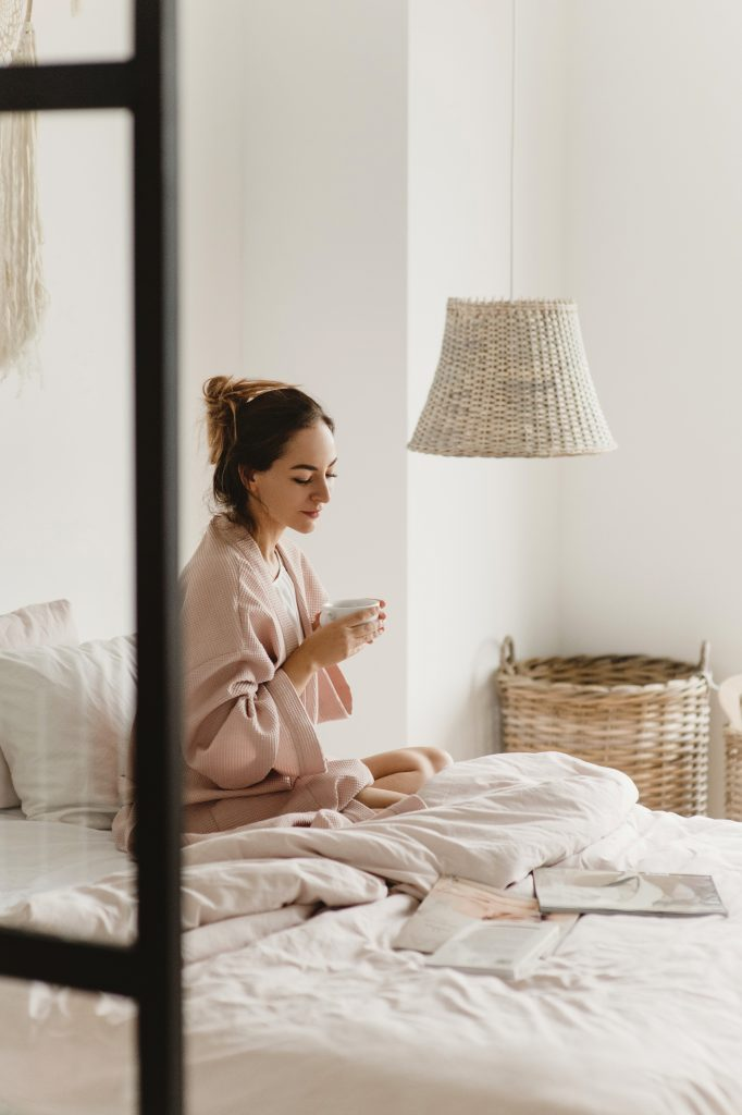 girl in bed with a cup of coffee wants to stay postitive