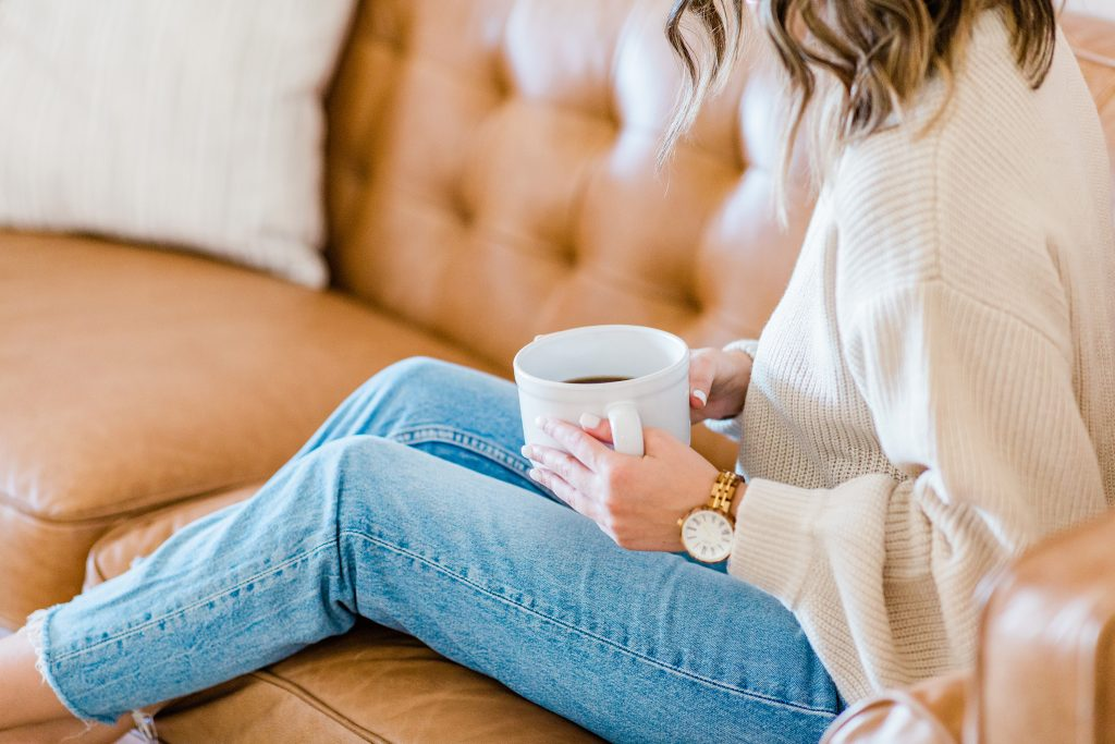 Girl sitting on couch with a cup of coffee tries to stay positive