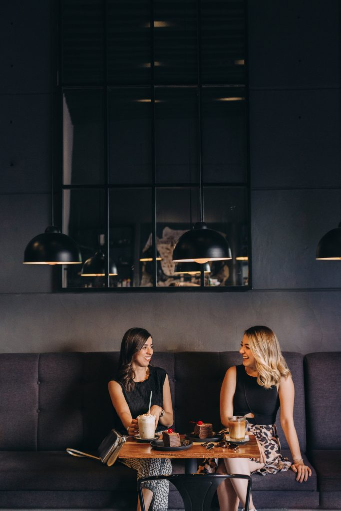 two girls sitting in a cafe which helps to stay motivated