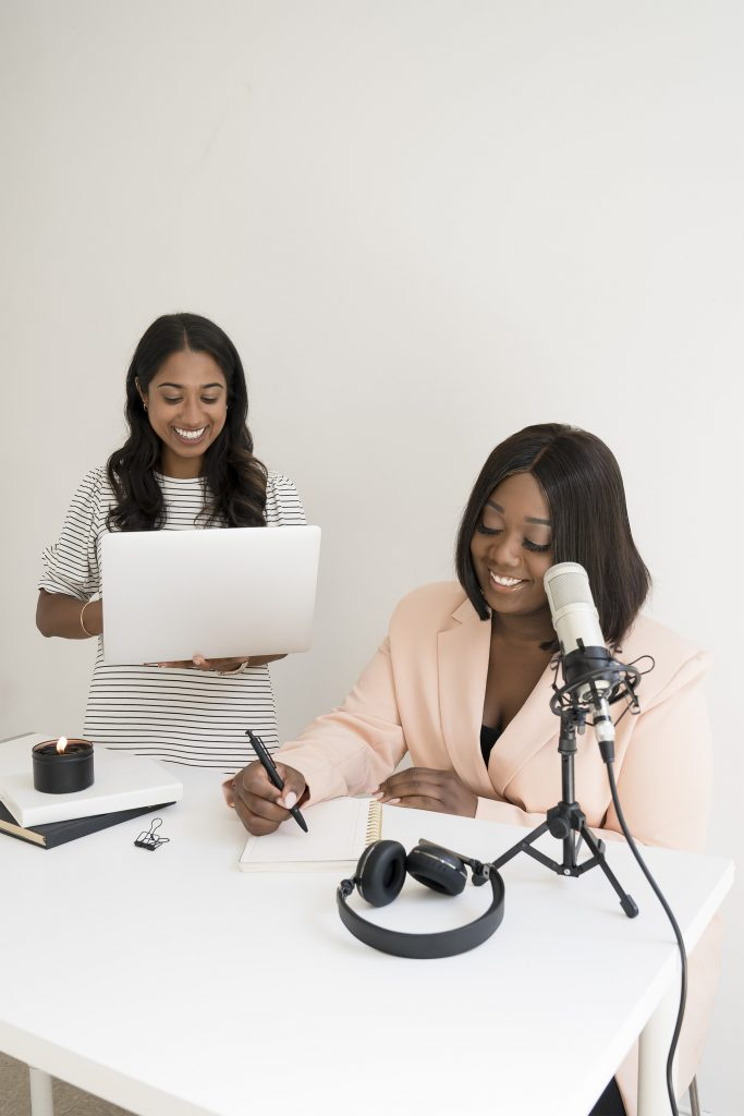two girls at a desk preparing for a podcast, and show how to be more productive with having fun