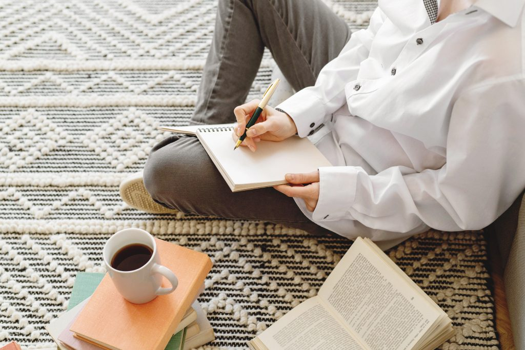 girl sitting on the floor with coffee and journals to get clear how to find your purpose