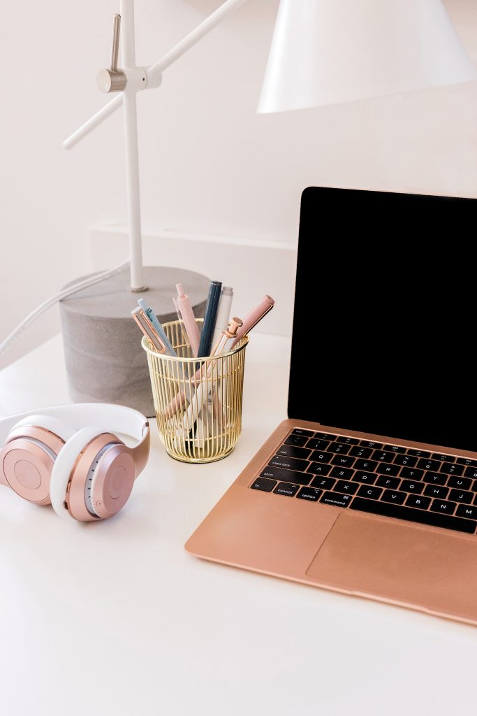 laptop, stationary, and earphones to show how to build good habits in all areas of life